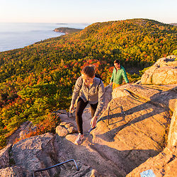 """Hikers make their way up """"The Beehive"""" in fall in Maine's Acadia National Park."""