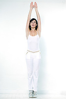 beautiful young woman exercising aerobics stretching arms tiptoe on studio isolated white background doing her workout stretch