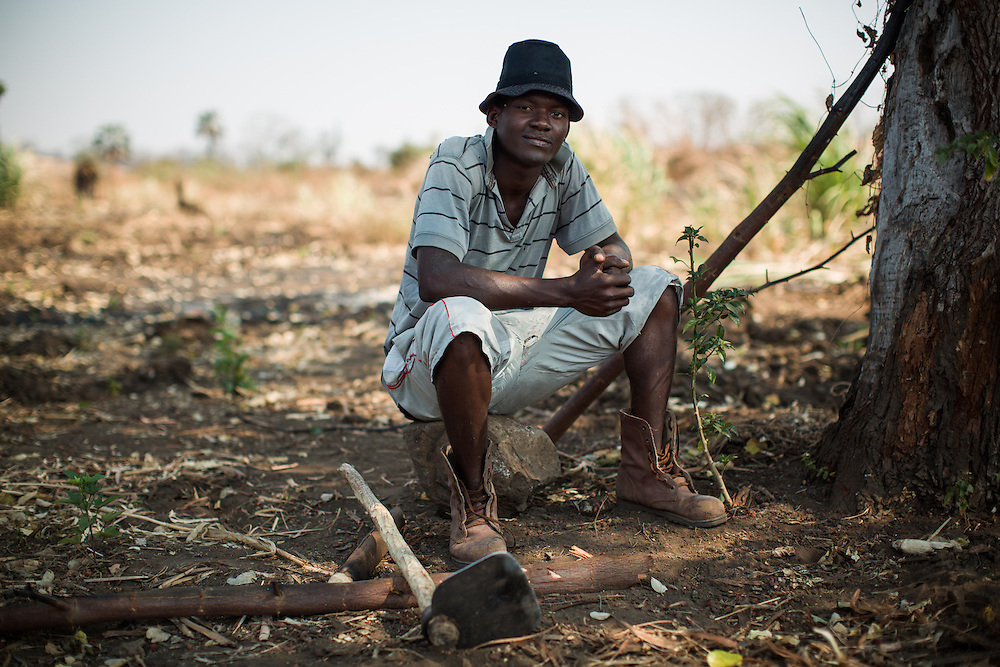 Russel Zuva lived in Zimbabwe where he also received his education. Now he is not able to find a job in the Cateme area and helps his grandmother Siminaria on their field. The farmland given to the resettled families is about a two hour walk from their houses and highly unproductive - the soil is not fertile and very rocky. Cateme village, a Vale resettlement compound with over 700 families from the villages of Chipanga, Mitete, Malabue-Gombe and Bagamoyo. Vale deliberately divided the communities in two with employed villagers moving to 25 de Setembro since it is closer to Moatize and the coal mine. The unemployed were resettled to Cateme, 40 km from the original town. While the most immediate problem of the community is the enormous distance to Moatize, their old habitat, they also suffer from unproductive farmland which can only be reached via a two hour walk, no access to markets and infrastructure and poorly constructed houses not fitted to the people's needs with temperatures inside reaching as high as 65° C due to the construction with tin clad roofs and missing isolation.