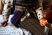 Traditional Tibetan dress of a Tamang woman in the Langtang Valley, Nepal, 30th May 2009. The 'Pangden' (striped, woven woollen apron) is belted with an ornate brass belt from which hangs a silver medicine spoon.<br /> <br /> According to Dorothea Stumm, a glaciologist at the Nepal-based International Centre for Integrated Mountain Development, a massive hanging glacier cracked when an earthquake struck at 11.56am on the 25th April 2015. The ice formed a cloud that gathered snow and rocks and then funnelled down the mountain, burying Langtang village, and creating an enormous pressurised blast. 400 residents of the village and up to 100 trekkers are believed to have been killed.<br /> <br /> PHOTOGRAPH BY AND COPYRIGHT OF SIMON DE TREY-WHITE<br /> <br /> + 91 98103 99809<br /> email: simon@simondetreywhite.com<br /> photographer in delhi