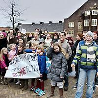 Nederland, Amsterdam , 18 februari 2012..Gezamelijke actie van z.g. nieuwkomers en autochtone Amsterdam Noord bewoners  van  het Zonneplein en omgeving tegen de leegloop van winkelpanden en dreiging tot sluiting van het Zonnehuis..Dinsdagavond vond er in het Zonnehuis in Noord een vergadering plaats, waarin de toekomst van het Zonnehuis en de winkels op het Zonneplein besproken werden..Tijdens de vergadering werd bekend dat de exploitanten van het theater een huurachterstand hebben opgebouwd, die zij op korte termijn niet kunnen inlossen. De verhuurder Stadsherstel wil de exploitanten geen extra tijd geven: '1 maart moet het geld zijn overgemaakt, anders gaat de stekker eruit', zegt een van de exploitanten..Bij de vergadering waren buurtbewoners en ondernemers van het Zonneplein aanwezig. Al langere tijd kampen ondernemers van hetZonnepleinmet problemen. De concurrentie van grote winkels neemt steeds meer toe en steeds meer kleine kruidenierszaken, slagers en bakkers verdwijnen uit het straatbeeld..Op de foto hebben zich tientallen bewoners uit de buurt verzameld voor de komst van AT5 en een fotograaf van een krant...Er werd gezongen en geposeerd..Foto:Jean-Pierre Jans