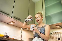 Beautiful young woman pouring coffee in the kitchen, Munich, Bavaria, Germany