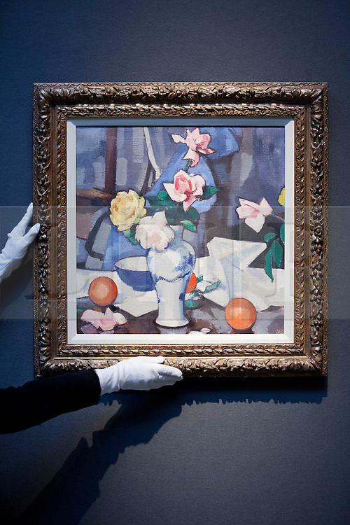 """© Licensed to London News Pictures. 18/11/2013. London, UK. A member of Christie's staff adjusts """"Still life with roses in a blue and white vase"""" (est. GB£300,000 - 500,000), painted by Scottish artist John Peploe in the early 1920's, at the press view for a sale of modern British and Irish art at Christie's St James' auction house in London today (18/11/2013). The sale is set to take place on Wednesday the 20th and Thursday the 21st of November 2013. Photo credit: Matt Cetti-Roberts/LNP"""