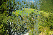 Tyrolean Alpine landscape as seen through a curtain of water from behind a waterfall. Photographed in Stubai Valley, Tyrol, Austria