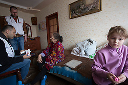 Doctor Khachatur Malakyan (l) and nurse Andrei Bogma (2nd l) during an MSF home visit in Debaltsevo. Lina and her mother live in a small apartment with Lina's two young daughters and her husband. They try to care for their grandmother who suffers from Parkinson's disease.