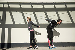 Man and woman in sportswear doing stretching outdoors