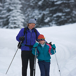 A woman and her young daughter cross-country skiing at the AMC's Little Lyford Pond Camps in Maine's Northern Forest.  Near Greenville.
