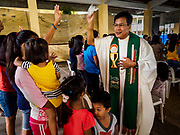 28 JANUARY 2018 - LEGAZPI, ALBAY, PHILIPPINES: Monsignor NOE THOMAS sprinkles holy water on people after a Catholic mass at the evacuation shelter for people from Barangay (community) Matanag in Albay Central School in Legazpi. Monsignor Thomas is the parish priest at St. Gregory the Great Cathedral in Legazpi. People from the community have been in the shelter since Mayon volcano started erupting two weeks ago. There are about 500 families at the shelter, around 2,000 people. More than 80,000 people have been evacuated from communities around the volcano and are living in shelters and camps outside of the evacuation zone. The Philippine government is preparing to house the people for up to three months.      PHOTO BY JACK KURTZ
