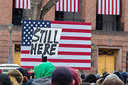 "Brooklyn, NY - 2 March 2019. A sign reading ""Still Here"" is raised in front of the American flag at Bernie Sanders' first rally for the 2020 presidential primary at Brooklyn College."