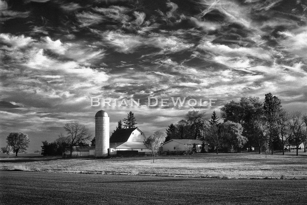 Sunlight casts a pleasing light on a barn and silo just before low clouds overtake the sky.   Aspect Ratio 1w x 0.667h