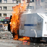 A protester takes cover after throwing a Molotov cocktail at a water cannon during clashes with riot police in Istanbul's Taksim square on June 11, 2013. Turkish Prime Minister Recep Tayyip Erdogan on June 11 said three protesters and one police officer have been killed in nearly two weeks of nationwide unrest against his Islamic-rooted government. Photo by AYKUT AKICI/TURKPIX