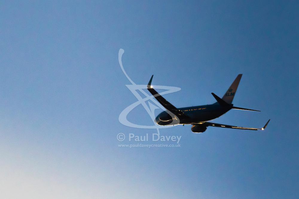 A KLM Boeing 737-800 departs London Heathrow's runway 27L as evening descends