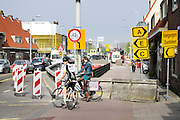 In Utrecht staan twee vrouwelijke fietsers te wachten tot ze bij een wegomleiding een drukke weg kunnen oversteken.<br /> <br /> Utrecht  two female cyclists are waiting until they can cross a busy road at a road construction