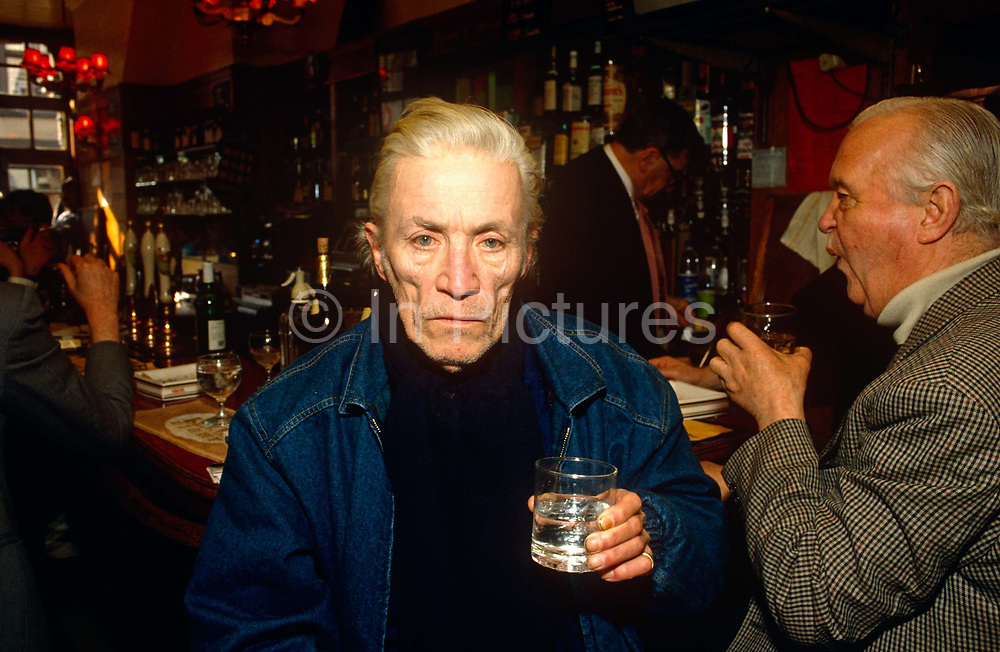 """The noted barfly, low-life and writer Jeffrey Bernard (1932 - 1997) is seen holding a drink in his favourite position at the Coach and Horse pub in Greek Street, London's Soho. Around him are his drinking buddies and even in the background, the celebrated landlord of this bohemian drinking hole, Norman Balon known as London's rudest landlord. The interior of the pub was recreated on stage for the Keith Waterhouse 's biographical play about Bernard's life """"Jeffrey Bernard is Unwell"""". The play was successful and Balon's memoirs followed entitled You're Barred, You Bastards (ISBN 0283997621). Barnard was a British journalist, best known for his weekly column """"Low Life"""" in the Spectator magazine, but also notorious for a feckless and chaotic career and life of alcohol abuse."""