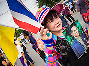 05 AUGUST 2013 - BANGKOK, THAILAND: An Anti-government protestor waves the Thai national flag and the flag of the Thai monarchy while she holds up a picture of Bhumibol Adulyadej, the King of Thailand, during an anti-government protest in Bangkok. About 500 people, members of the  People's Army against Thaksin Regime, a new anti-government group, protested in Lumpini Park in central Bangkok. The protest was peaceful but more militant protests are expected later in the week when the Parliament is expected to debate an amnesty bill which could allow Thaksin Shinawatra, the exiled former Prime Minister, to return to Thailand.    PHOTO BY JACK KURTZ