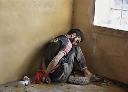 July 9, 2017 - Mosul, Iraq - Hands tied with a red sash, MOHAMMED ABD HAMAD, 20 long with two others surrended after being surrounded by ISOF Special Forces who believe they are ISIS fighters in West Mosul amid ruins of the city. They say they are not. They are held captive at a base near the front line. (Credit Image: © Carol Guzy via ZUMA Wire)