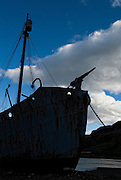 Abandoned whaling ship named Pertel, rusting on the shore of Grytviken, South Georgia. Silhouetted against the sky is a ship and harpoon that helped nearly make whales extinct.