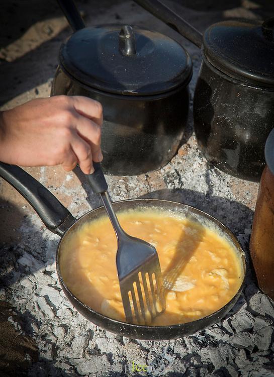 Close up of scrambled eggs on campfire, human hand during preparations, Zambezi River, Zambia