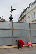"A lady stoops to fetch something from her bag at a temporary construction hoarding beneath the partially hidden statue of Eros, the world famous London Victorian-era landmark, Eros in Piccadilly Circus, on 25th February 2020, in London, England. Eros, or the Shaftesbury Memorial Fountain is located at the southeastern side of Piccadilly Circus in London, United Kingdom. Moved after World War II from its original position in the centre, it was erected in 1892–1893 to commemorate the philanthropic works of Lord Shaftesbury, who was a famous Victorian politician and philanthropist. The monument is surmounted by Alfred Gilbert's winged nude statue generally, though mistakenly, known as Eros. This has been called ""London's most famous work of sculpture."""
