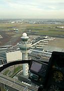 Nederland, Haarlemmermeer, Schiphol, 15-02-2007;  Schiphol airport, zicht op stationsgebouw (terminal) van de luchthaven met verkeerstoren, verschillende van de pieren met 'slurfen' ( voor in- en uittappen passagiers) zijn tevens in beeld; ook in beeld het instumentarium van de Hughes 300 C helikopter (GPS, hoogtemeter); in de achtergrond Schiphol-Oost; helikopter; helicopter, cockpit, vliegverkeer, vliegen, verkeersleiding, infrastuctuur, verkeer en vervoer, start, landing.luchtfoto (toeslag); aerial photo (additional fee required); .foto Siebe Swart / photo Siebe Swart