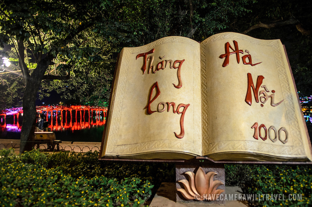 An art sculpture in the form of a book celebrates the 1000th anniversary of the founding of Hanoi on the banks of Hoan Kiem Lake. In the background is the red The Huc Bridge (Morning Sunlight Bridge).