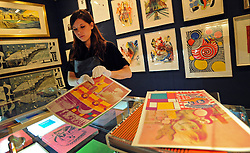 © Licensed to London News Pictures. 25/11/2011, London, UK. A Bonhams worker sorts through a portfolio of 100 prints by Eduardo Poalozzi, estimated to fetch 2,000 - 3,000 GBP. Preview of Bonhams print sale today 25 November 2011. 'Single dollar' works by Andy Warhol feature in Bonhams' print sale which is being hung for viewing. The signed prints, estimated at between £15,000- 20,000, represent the link Warhol often made between art and money, underlined by the high prices paid for them by collectors at the time and ever since. Photo credit : Stephen Simpson/LNP