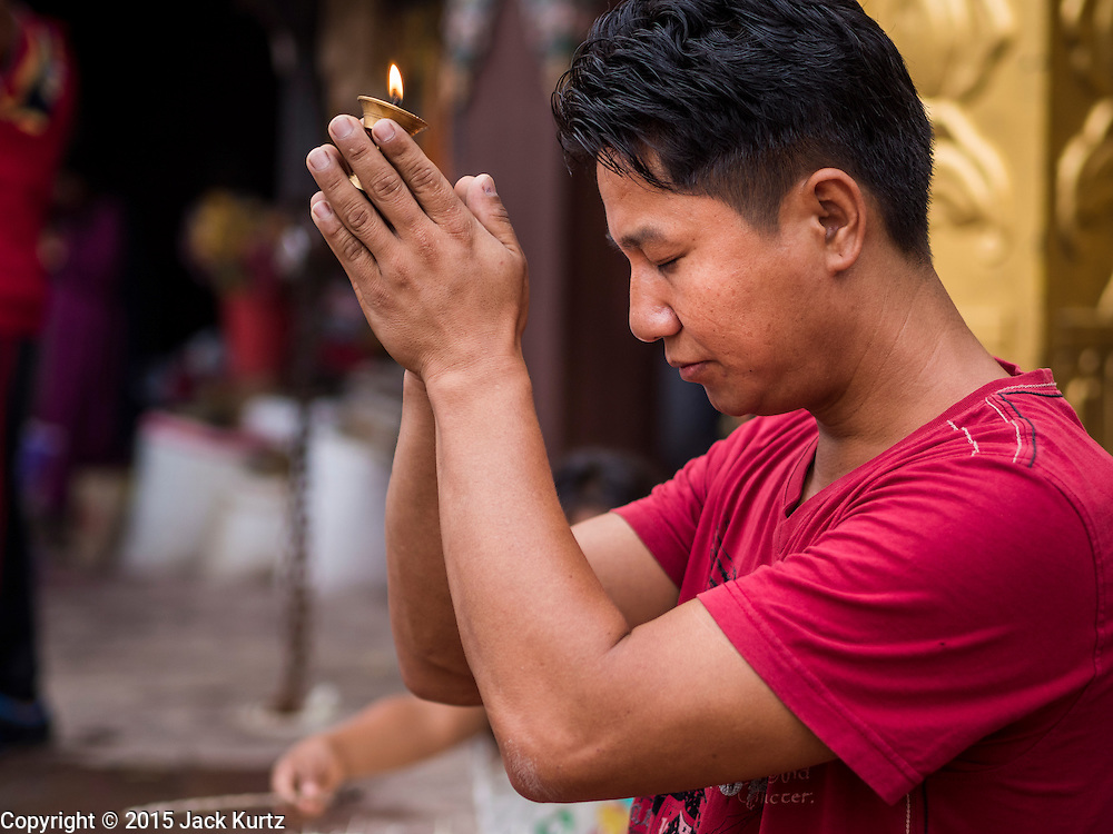 31 JULY 2015 - KATHMANDU, NEPAL: A man prays with a butter lamp during the full moon processions at Bodhnath Stupa. Bodhnath Stupa in the Bouda section of Kathmandu is one of the most revered and oldest Buddhist stupas in Nepal. The area has emerged as the center of the Tibetan refugee community in Kathmandu. On full moon nights thousands of Nepali and Tibetan Buddhists come to the stupa and participate in processions around the stupa. The stupa was heavily damaged in the earthquake of 25 April 2015 and people are no longer allowed to climb on the stupa, now they walk around the base and pray with butter lamps.   PHOTO BY JACK KURTZ