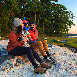 A young family takes in the sunrise after a night of camping on Lanes Island in Casco Bay. Yarmouth, Maine.