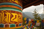 Large prayer wheel and prayer flags on the trail leading to the Taktsang Monastery, Bhutan