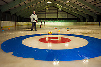 "Margo Weeks sweeps her team mates stone into the ""house"" during the first night of curling with Gilford Parks and Rec at the Arthur Tilton Ice Rink on Thursday evening.  (Karen Bobotas/for the Laconia Daily Sun)"