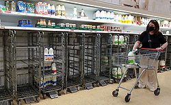 © Licensed to London News Pictures. 03/08/2021. London, UK. A shopper wearing a face covering walks stands next to empty trolleys of fresh milk in Sainsbury's, north London. It has been reported that Britain could face a shortage of milk supplies and these are likely to continue for several months, due to a lack of lorry drivers. UK's biggest milk processor, Arla Foods UK, has said that a number of individual stores have missed deliveries due to the pingdemic. Photo credit: Dinendra Haria/LNP