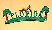 """Palm trees and a nude decorate a vintage (possibly 1940s or '50s), metal,  """"Florida Land of Sunshine"""" sign fixed to an outside wall of a small apartment building in Miami Beach's North Beach neighborhood"""