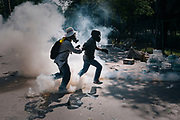 A protester kicks a tear gas canister back towards police lines during a stand-off between anti-Government protesters and police at Government House in Bangkok.