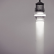 The Point Arena Lighthouse emerging from the fog along the Mendocino Coast of California.