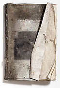 book that is blackened by smoke from a fire further damaged by water and covered with dust
