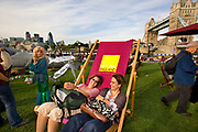 2 girls laughing on giant deckchair promoting England, Potters Bar field, Tower Bridge, Thames Festival 08, along the southbank of the Thames. September 2008