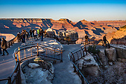 Visitors gather to see sunset at Mather Point Overlook, Grand Canyon National Park, Arizona, USA. Starting at least 5 to 17 million years ago, erosion by the Colorado River has exposed a column of distinctive rock layers, which date back nearly two billion years at the base of Grand Canyon. While the Colorado Plateau was uplifted by tectonic forces, the Colorado River and tributaries carved Grand Canyon over a mile deep (6000 feet), 277 miles  long and up to 18 miles wide.