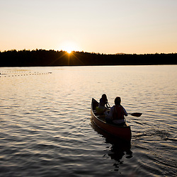 A woman and her daughter canoeing at sunset at White Lake State Park in Tamworth, New Hampshire.