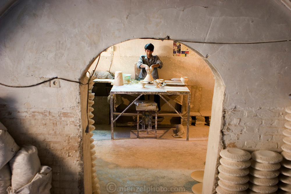 """Ghasem Imami, 21, a potter working for several years despite his young age, forms one of many he will create during the course of his workday at Morvarid (Pearl) Pottery Factory, Meybod,  Iran. (Also spelled """"Maybod"""")."""