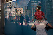 HSBC bank window mural with reflections of cityscape of Londoners and urban buildings in the background.