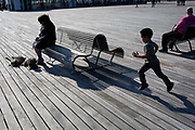 A running boy and the figures of visitors sitting on the benches of Hastings Pier, on 29th April 2017, at Hastings, East Sussex, England.