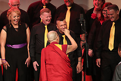 The Dalai Lama tugs on the beard of a chorister at the Millennium Forum, during a visit to Londonderry.
