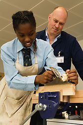 Woodwork teacher watching student using a plane in Design technology lesson,