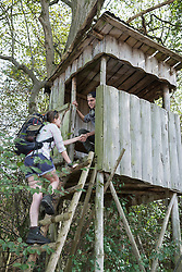 Teenage hiker helping woman to climb on lookout tower in a forest, Bavaria, Germany