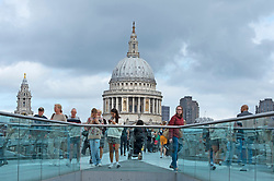 © Licensed to London News Pictures 29/08/2021. <br /> The City of London, UK. Dark clouds above St Paul's Cathedral in London as people walk over the Millennium Bridge. Photo credit:Grant Falvey/LNP