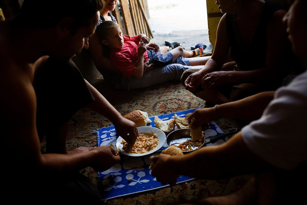 Stojan, left, and family eat lunch in the front room of their home in the Nova Gazela camp. Their normal meal is beans in gravy with bread.