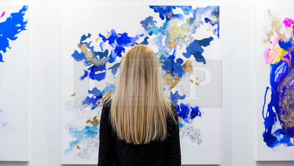 © Licensed to London News Pictures. 06/10/2016. London, UK. Artist, Corinne Natel stands in front of her artworks at the preview of Moniker Art Fair, part of London Art Week, taking place at the Old Truman Brewery, near Brick Lane.  Now in its seventh year, the fair embraces contemporary art from emerging and established artists, the majority of whom attend the fair in person in order to meet potential collectors and to show their work. Photo credit : Stephen Chung/LNP