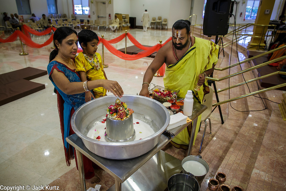 10 AUGUST 2012 - PHOENIX, AZ:    A Hindu priest helps a mother and child make an offering to a diety during the celebration of Janmashtami at Ekta Mandir, a Hindu temple in central Phoenix. Janmashtami is the Hindu holy day that celebrates the birth of Lord Krishna. Hindu communities around the world celebrate the holy day. In Arizona, most of the Hindu temples in the Phoenix area have special celebrations of the day..PHOTO BY JACK KURTZ