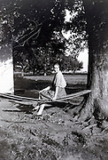 young adult girl sitting in rural garden setting USA 1920s