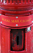 Close up of a  traditional red Royal Mail post box which has a 'Closed' notice attached over the posting slot. London, England.